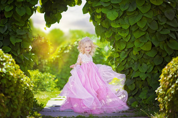Beautiful little girl in pink dress and tiara, in the park, in summer
