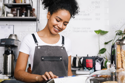 Smiling beautiful waitress using digital tablet in cafe Canvas