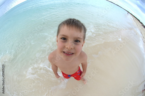 Fotografie, Obraz  Portrait of a cute boy standing on a beach - exaggerated fisheye image top view