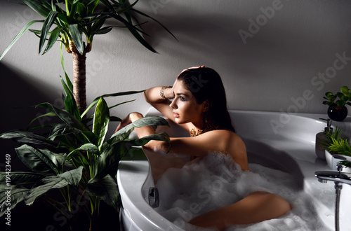 Young beautiful woman lying in bathtub and taking bath Wallpaper Mural