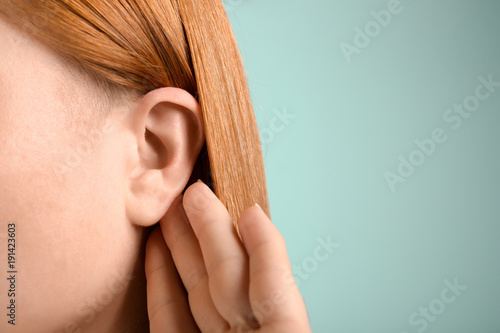 Photo  Young woman with hearing problem on color background, closeup