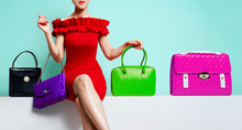 Woman With Red Dress Sitting With Many Colourful Purses.