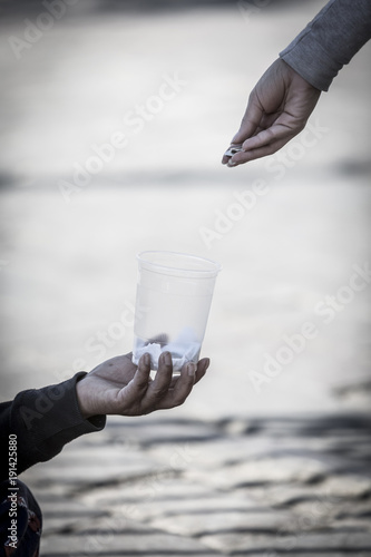 Photo  Woman's hand giving something  to a homeless