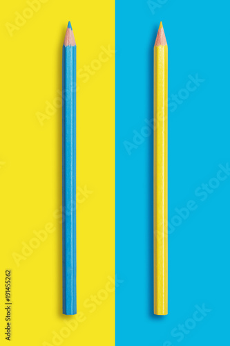 Photo two pencils of yellow and blue on a blue and yellow background, symbolize the op