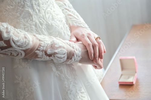 Women's hands on a white wedding dress. show her wedding ring with box in background.