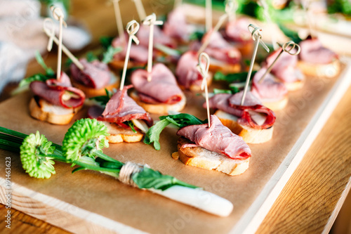 Foto op Aluminium Buffet, Bar Delicious catering banquet buffet table decorated in rustic style in the garden. Different snacks, sandwiches with ham and greenery on a wooden plate. Outdoor.