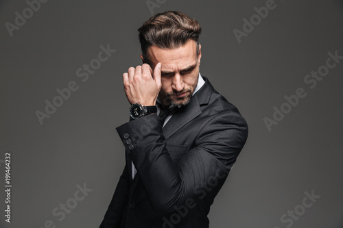 Fotografía  Portrait of handsome serious businessman in black suit posing on camera with fan