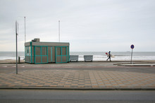 Lone Surfer In Neoprene Swimsuit Walking On Pavement To Empty Beach On A Cold Winter Overcast Day. The Hague, Netherlands