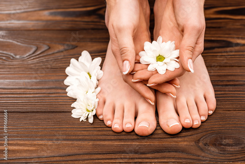 cropped view of female hands and feet with medicine and pedicure on wooden surface