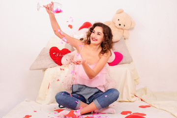 Obraz na płótnie Canvas Smiling young woman sitting on floor around hearts in lotus position pouring out paper hearts from wine glass.