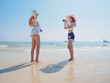 summer holiday,vacation,travel and people concept of smiling young women check a photo on beach over sea and blue sky background.Portrait of three young female friends walking on the sea shore looking