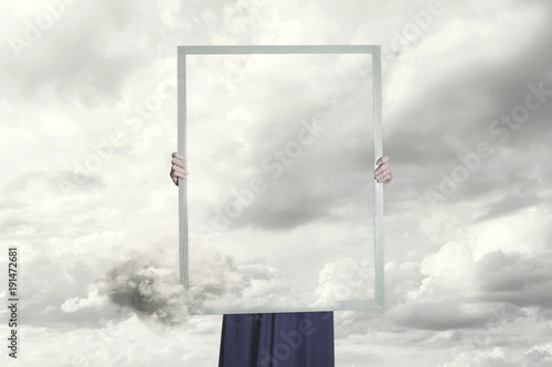 Fotografia, Obraz surreal moment of a woman hiding behind a picture of clouds equal to the landsca