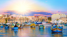 Beautiful Panorama Of Valletta Harbor In Malta, With Boats And Architecture Illuminated By Sunset Light