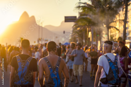Abstract blur view of young unidentifiable brazilians celebrating carnival at a sunset bloco street party on the Ipanema beachfront.