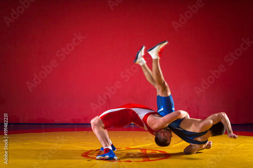 Obraz Two  strong men in blue and red wrestling tights are wrestlng and making a suplex wrestling on a yellow wrestling carpet in the gym. Wrestlers doing grapple. - fototapety do salonu