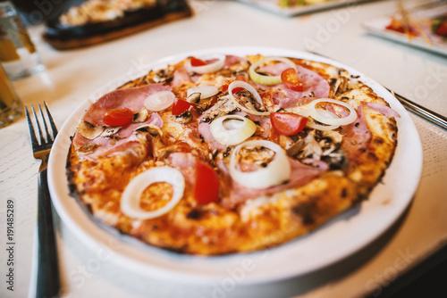 Plakat Wyśmienicie pizza z pomidorem i cebulą na białym talerzu przy restauracją podczas gdy przyjaciele ma lunch.