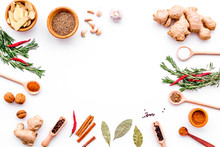 Colorful Dry Spices In Bowls And Spoons Near Ginger, Garlic, Rosemary, Laurel Leaf On White Background Top View Copy Space