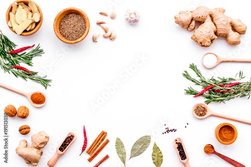 Obraz Colorful dry spices in bowls and spoons near ginger, garlic, rosemary, laurel leaf on white background top view copy space - fototapety do salonu