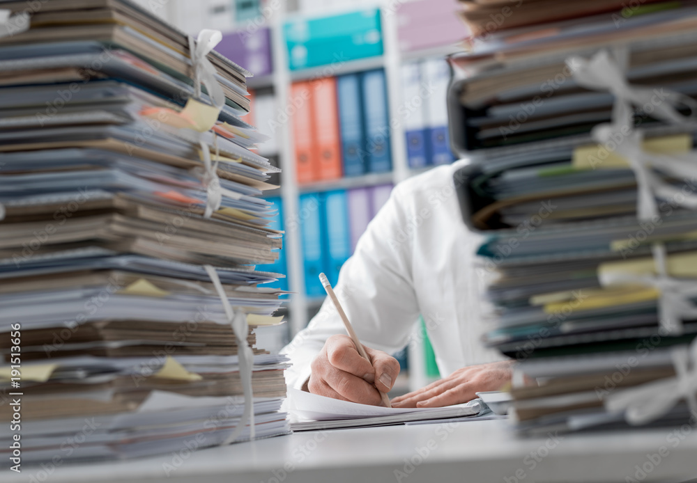 Fototapety, obrazy: Businessman working in the office and piles of paperwork