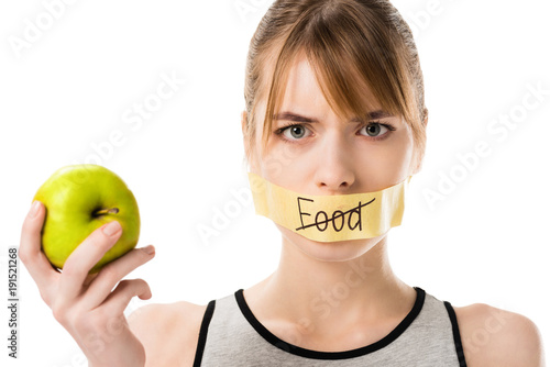 Photo young woman with stick tape with striked through word food covering mouth holdin