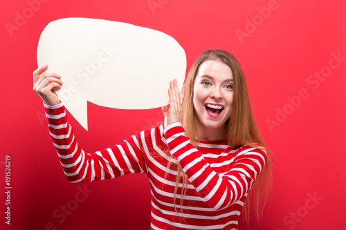 Young woman holding a speech bubble on a red background Poster