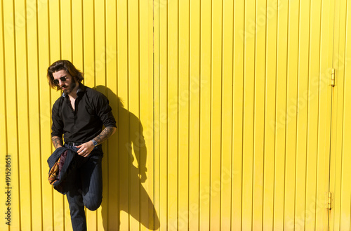 Man standing against yellow wall