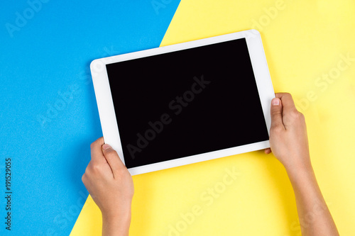 Kid hands with tablet computer on blue and yellow background