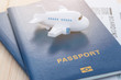 Small toy plane on top of a blue passport with boarding pass on a wooden background.