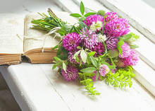 Bouquet Of Clover And Old Book On The Window.