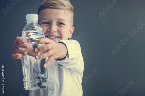 Fotografía  Happy boy holding bottle of water.