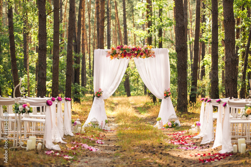 Fotografía  Beautiful elegant wedding decorations of place for ceremony outside in old wood with huge pines trees