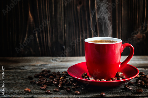 Fototapeta cup of fresh coffee with coffee beans on wooden table obraz