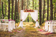 canvas print picture - Beautiful romantic festive place made with wooden square and floral roses decorations for outside wedding ceremony in green park. Wedding settings at scenic place. Horizontal color photography.
