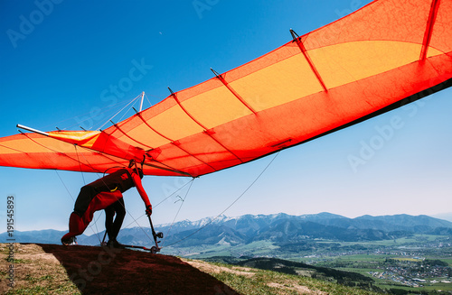 Man with hang-glider starting to fly from the hill top