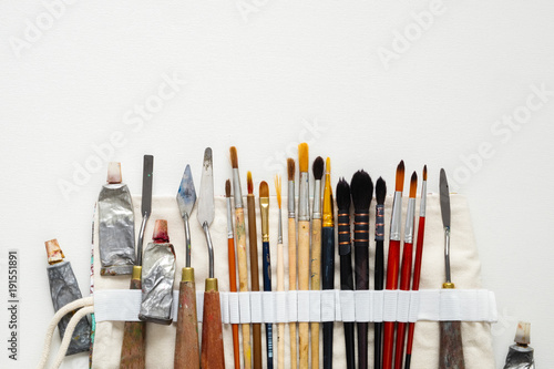 Paintbrushes, palette knifes and paint tubes in textile carry bag. A storage case filled of tools for professional artist work. Copy space for text.
