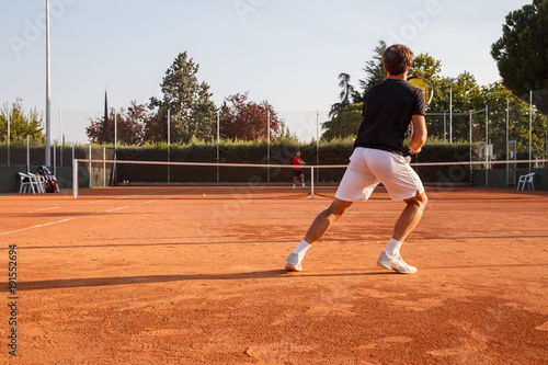Fotografia Professional tennis player playing tennis on a clay tennis court on a sunny day