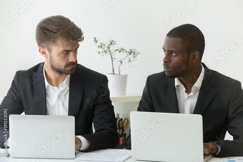 Photo Multiracial office rivals looking at each other with hate envy sitting with lapt