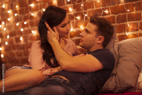 Young couple kissing and hugging in the bedroom. Such a romantic atmosphere.