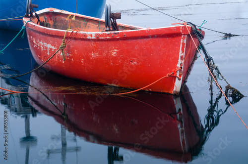 Photo  Bright Red Fishing Dory Moored to Blue Boat