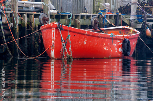 Photo  Bright Red Fishing Dory Tied to Dock