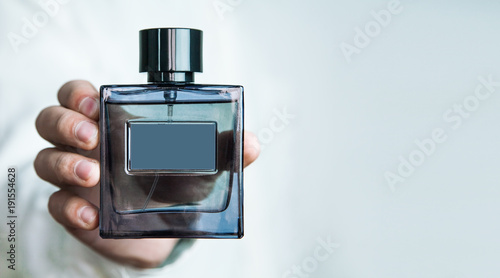 Fototapeta Man holding a bottle of perfume. obraz