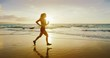 Athletic young woman running on the beach at sunset