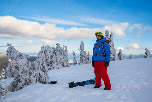 Poster Ontspanning Snowboarder relaxes on a mountain ridge