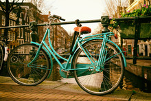 Beautiful Vingage Photo Of A Dutch Bicycle On A Bridge In Amsterdam With Buildings In The Background And Space For Text.