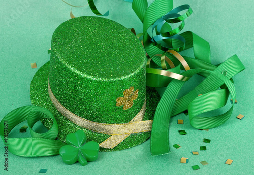 Fotografie, Obraz  Saint Patrick's Day image of sparkly green and gold leprechaun hat with curls of green and gold ribbon on a green background with confetti scattered around