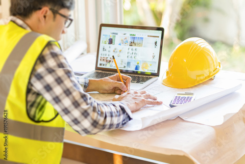 architect man working with laptop and blueprints,engineer inspection in workplace for architectural plan,sketching a construction project Canvas Print