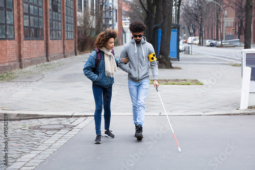 Fotografie, Tablou Woman Helping Blind Man While Crossing Road