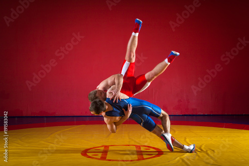 Obraz Two greco-roman  wrestlers in red and blue uniform wrestling  on a yellow wrestling carpet in the gym - fototapety do salonu