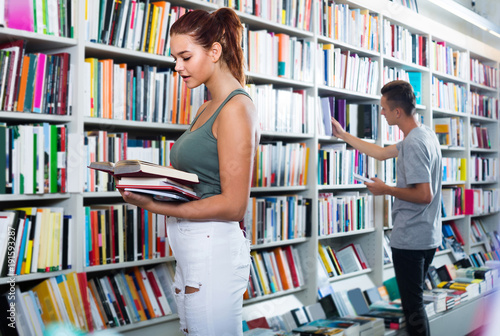 Foto  portrait of  teenage girl customer looking at open book standing among bookshelv