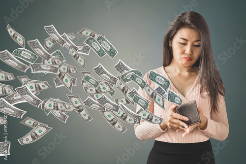 Fotografie, Obraz  unhappy and poor Asian woman holding  purse having problem with money flying awa